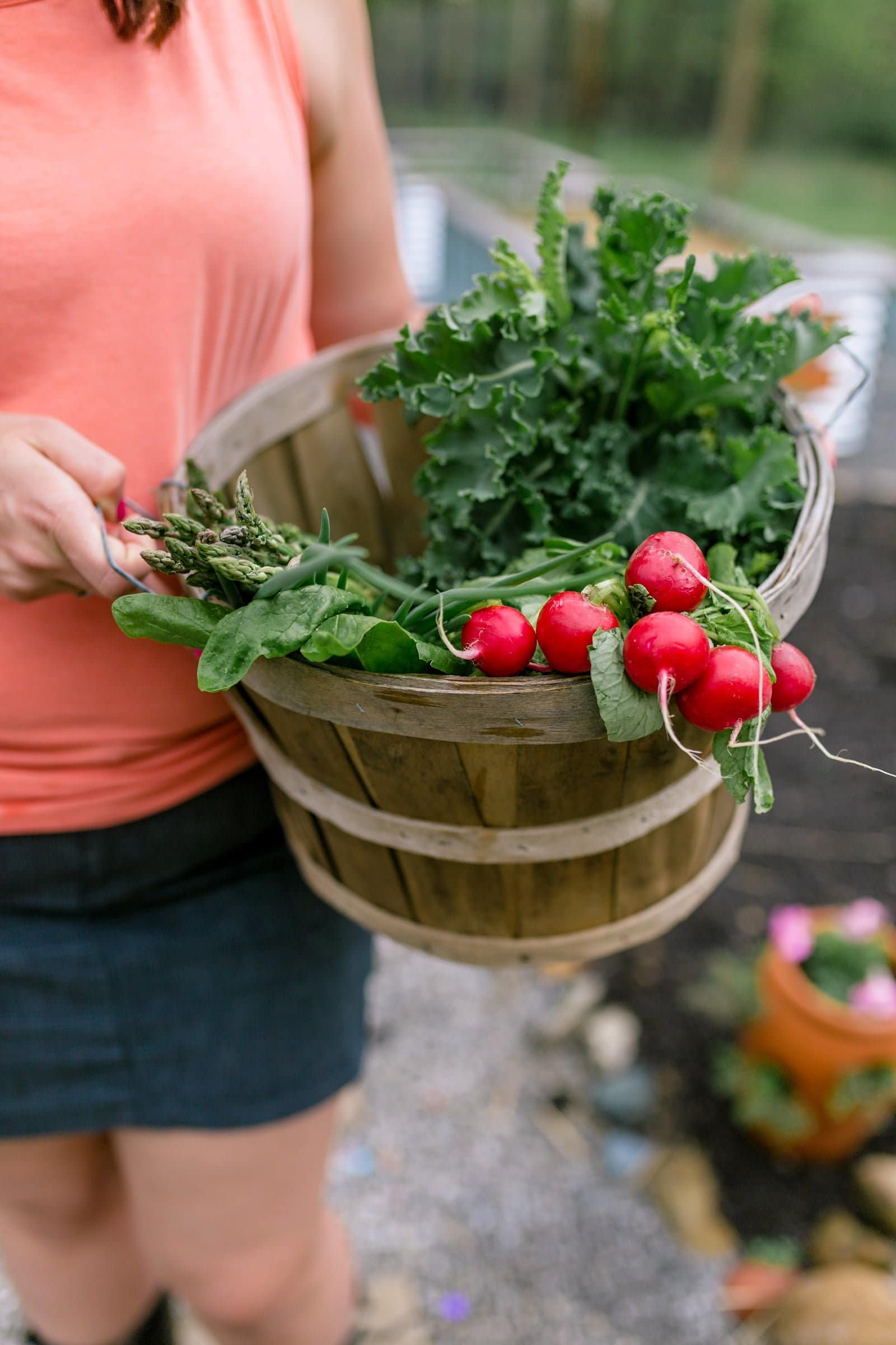 Woman in a coral shirt holding a basket of radishes and greens