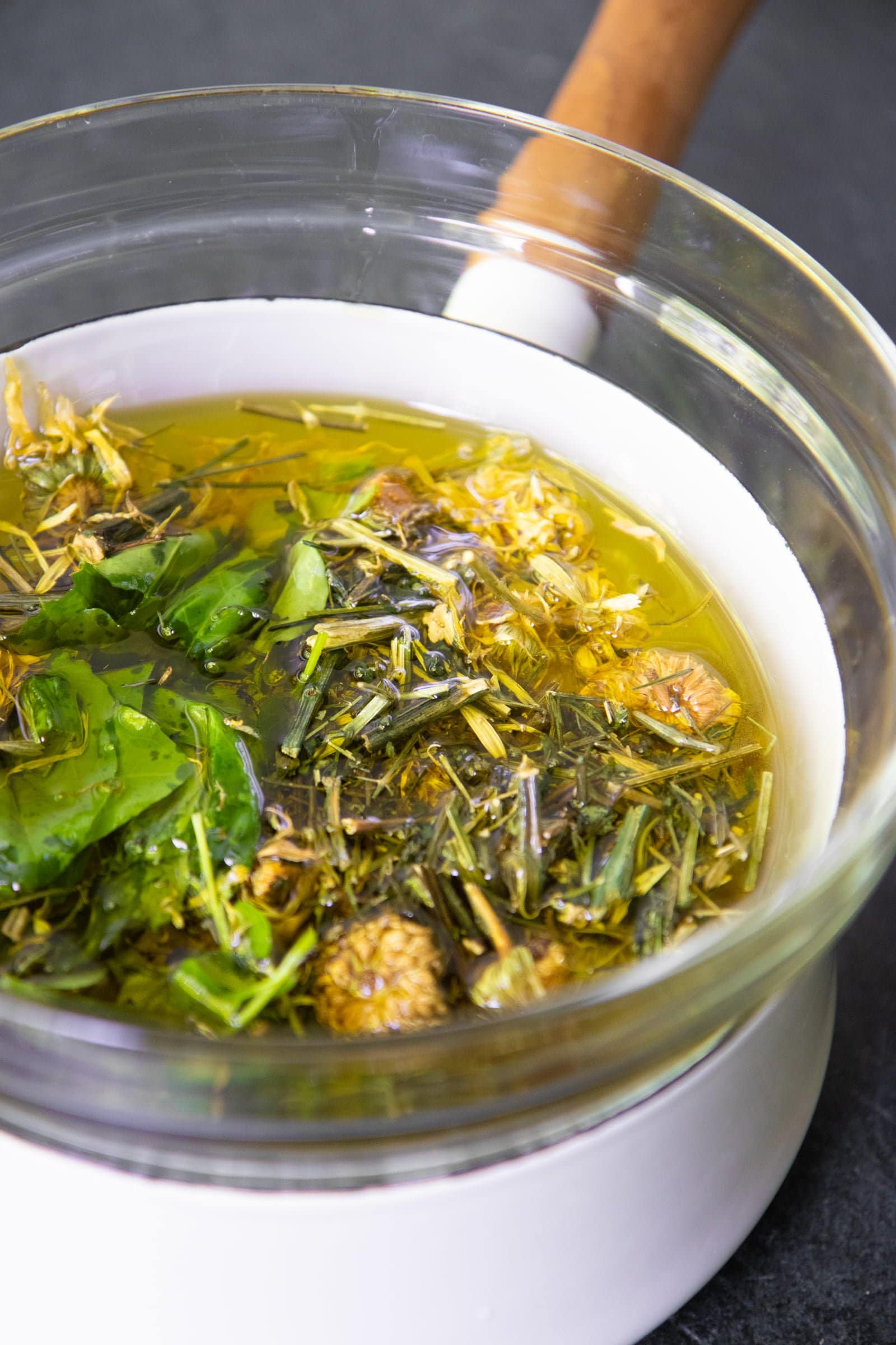 Glass bowl filled with herbs and oil set over simmering water, to infuse the oil