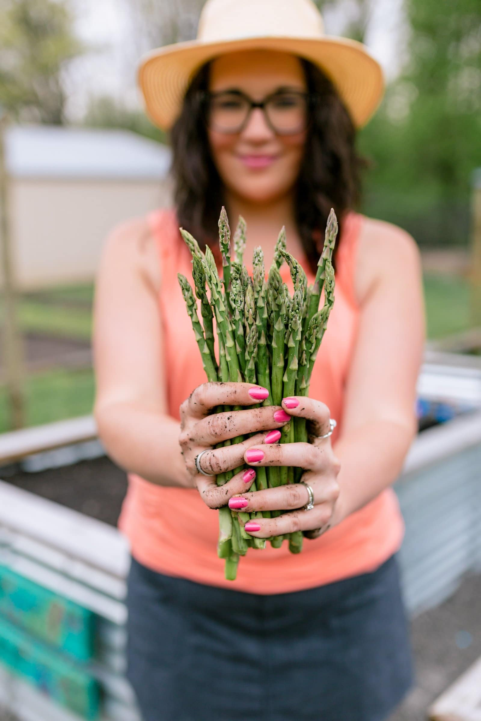 Brunette woman in a coral shirt holding out a bunch of asparagus in a garden