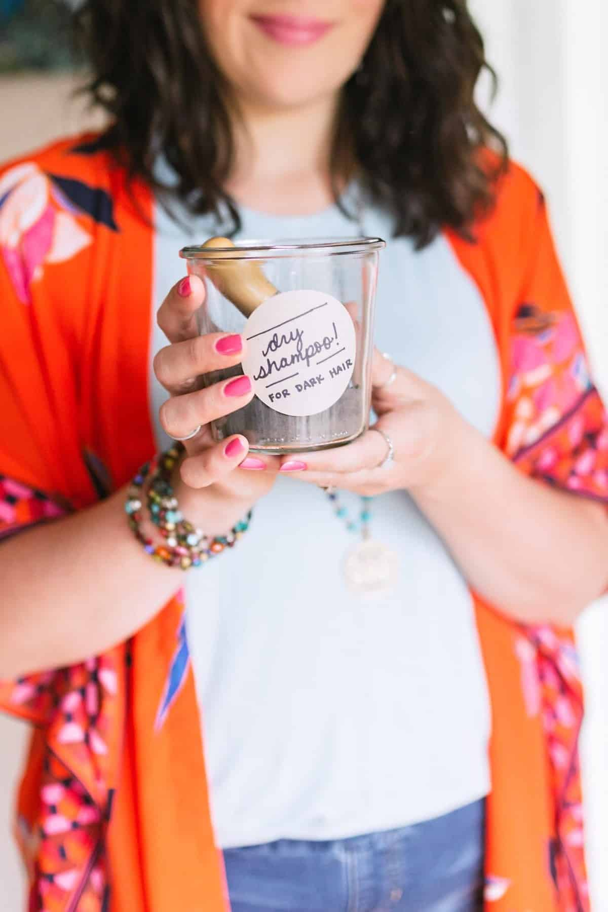"""Brunette woman in a neutral top and orange kimono holding a jar labeled """"dry shampoo"""" in both hands."""