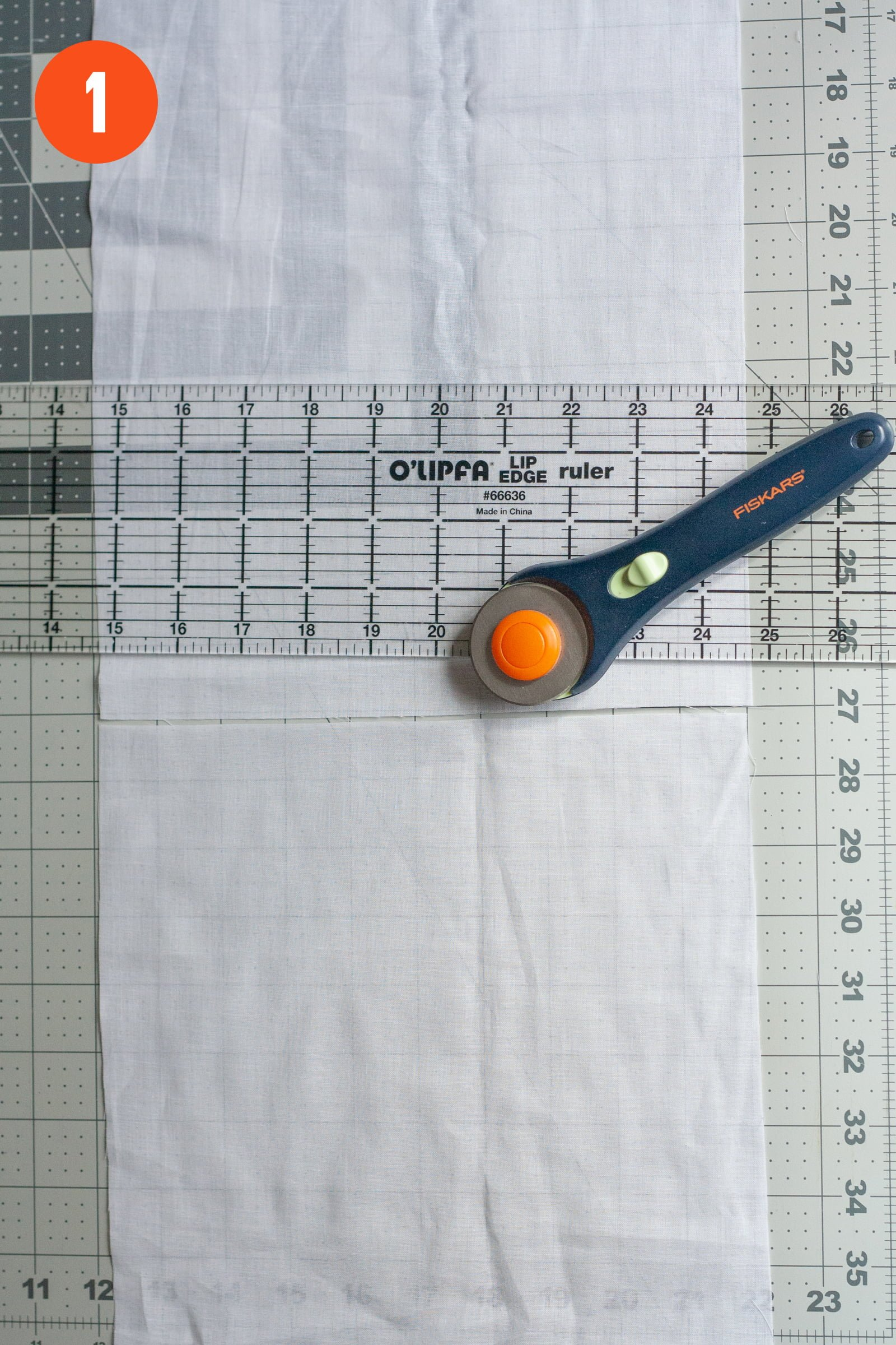 """Rotary cutter and ruler on top of a cut piece of cotton voile. Labeled with a """"1"""""""