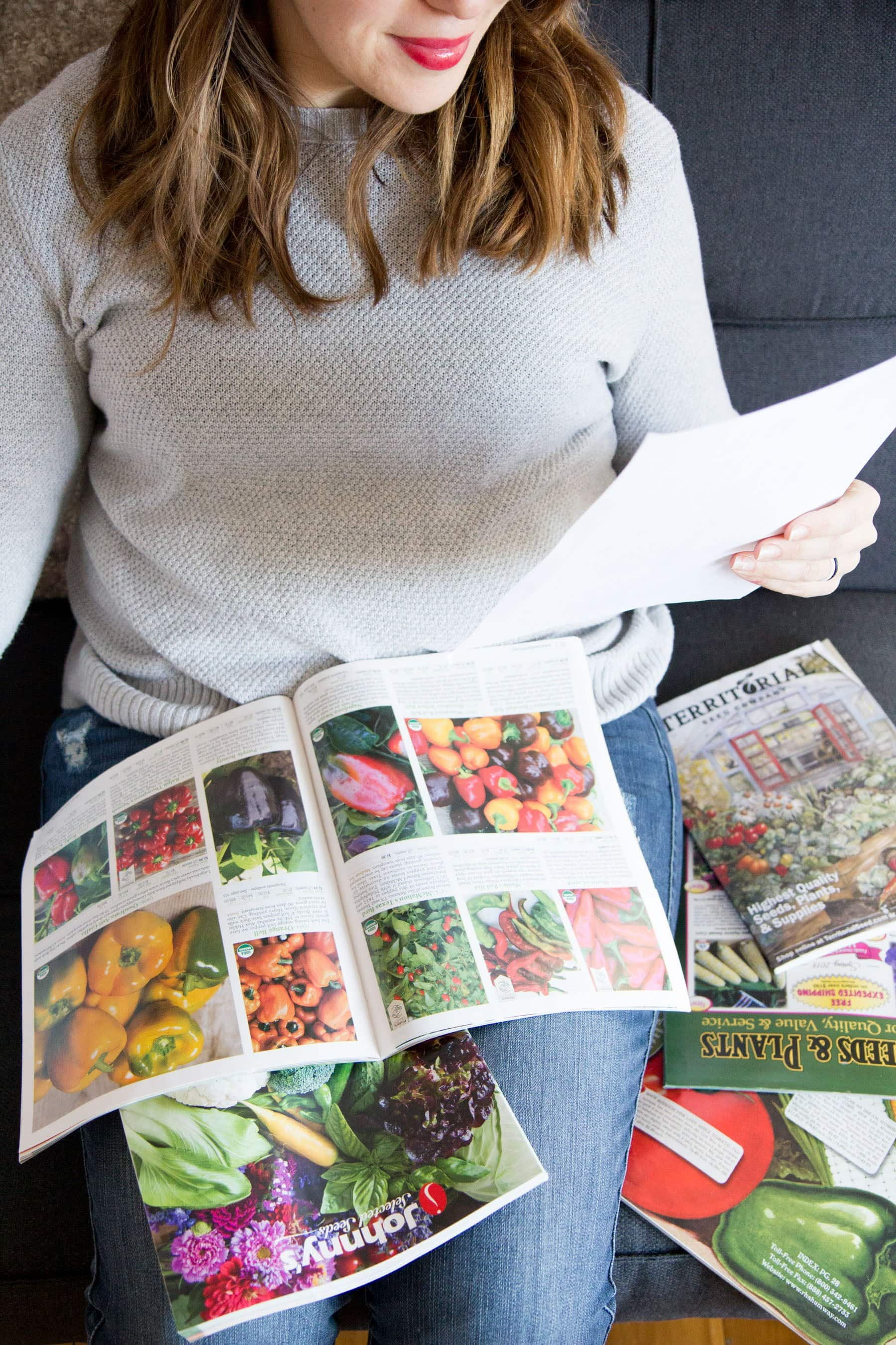 Woman in a gray shirt looking through seed catalogs for organic vegetable seeds