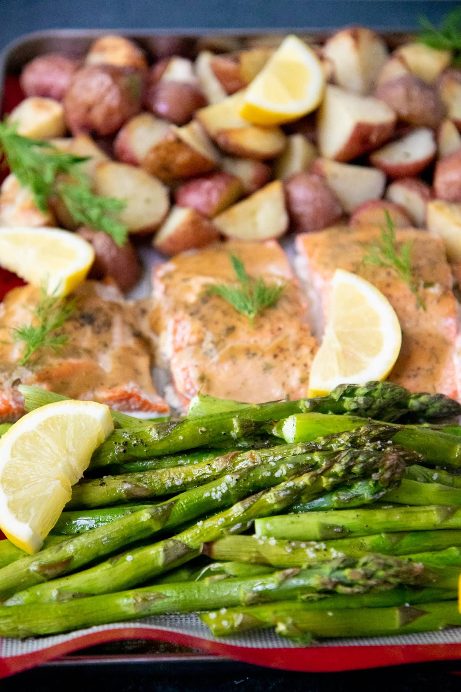Asparagus, salmon, and potatoes arranged on a baking sheet.
