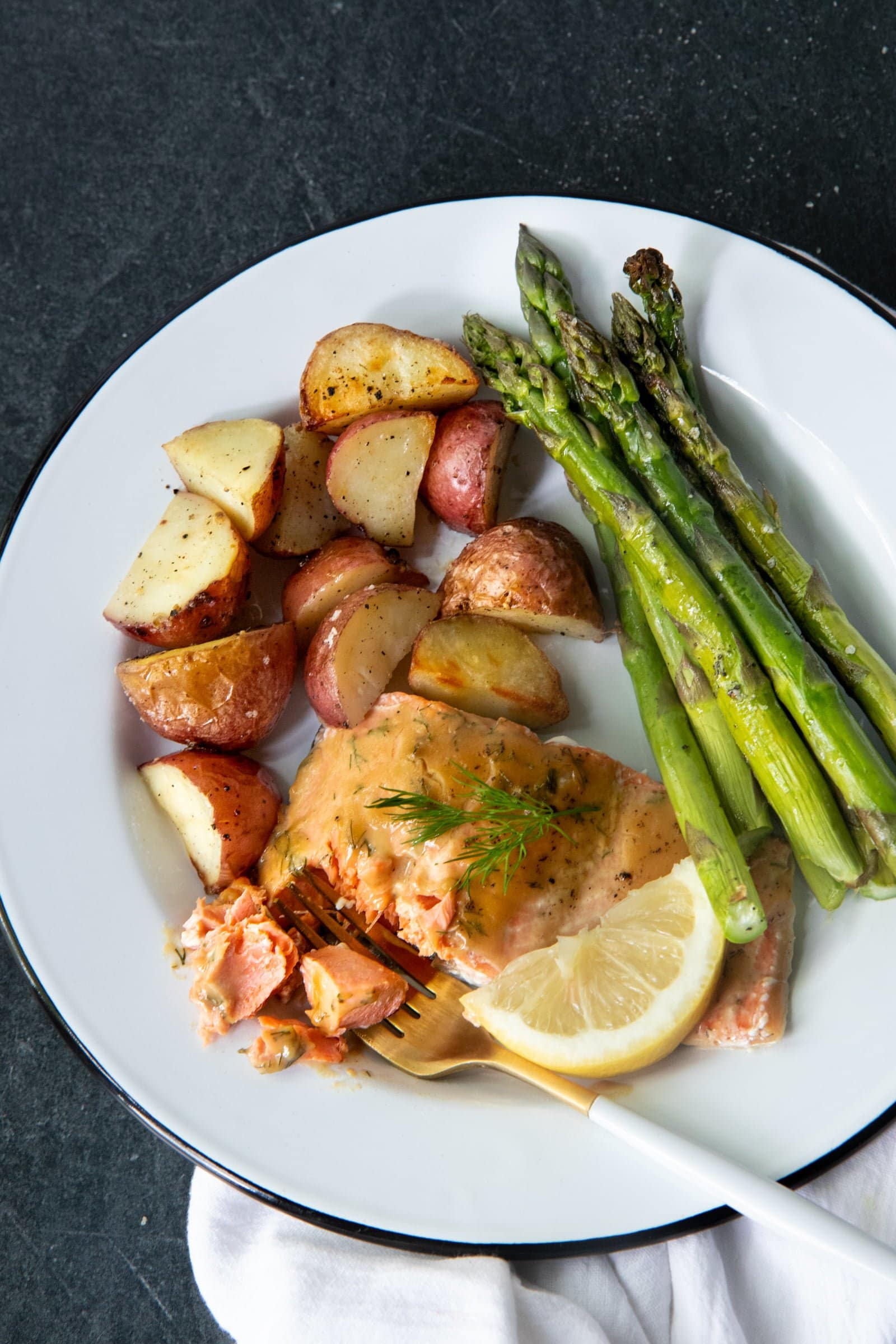 Mustard Maple Glazed Salmon, roasted asparagus, and roasted potatoes on a white plate with a fork.