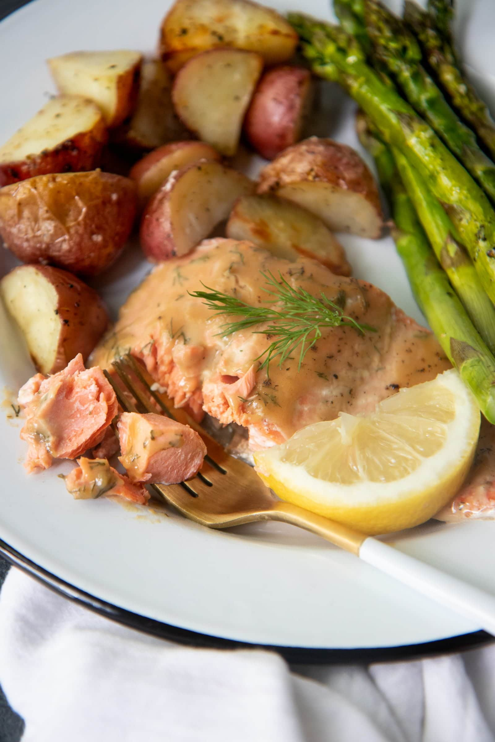 Mustard Maple Glazed Salmon, roasted asparagus, and roasted potatoes on a white plate with a white and gold fork.