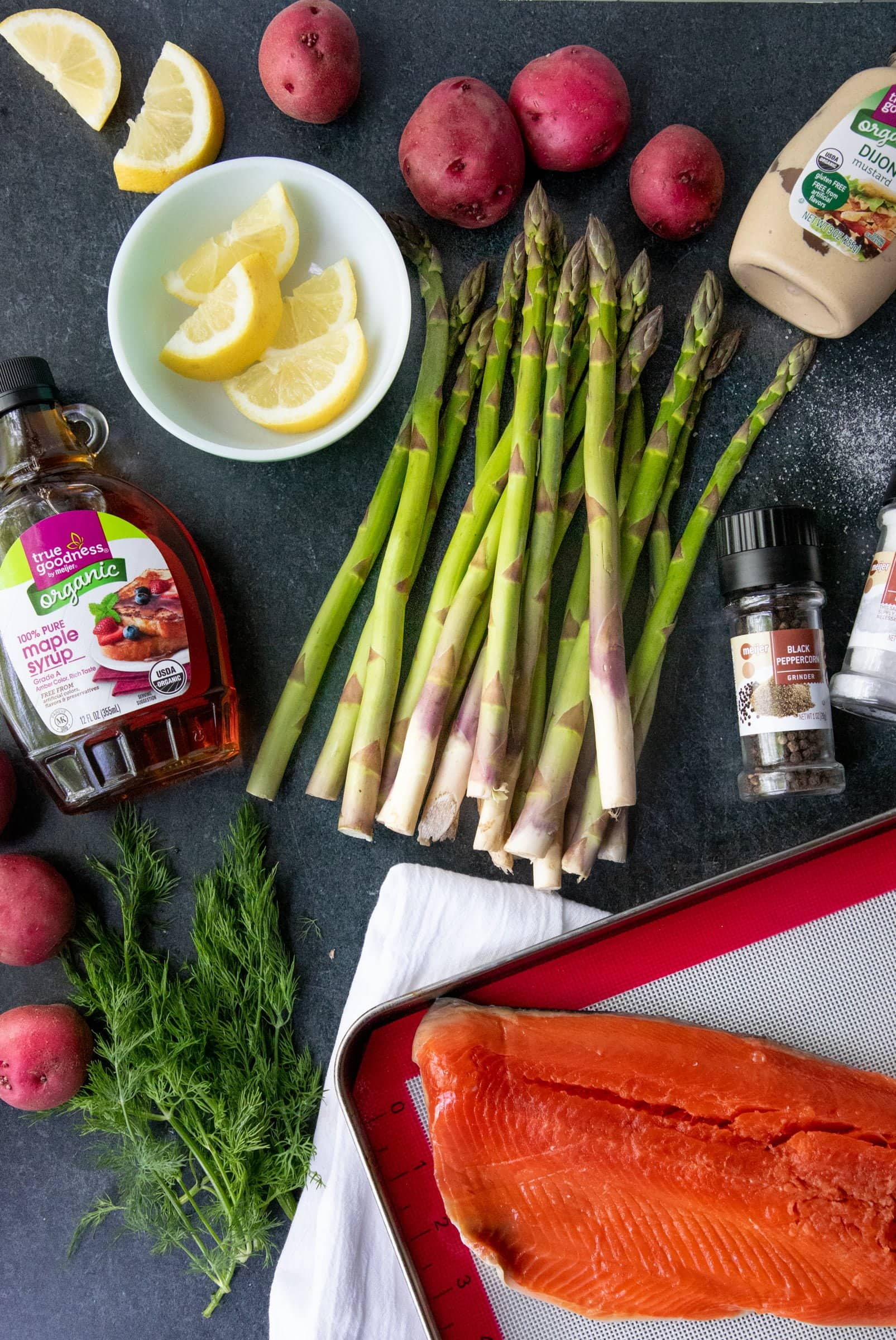 Ingredients for Mustard Maple Glazed Salmon and Asparagus on a gray background - salmon, asparagus, potatoes, maple syrup, dijon mustard, lemon slices, dill, salt, and pepper.