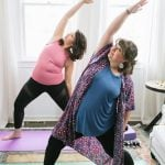 Two brunette women standing on yoga mats in a Reverse Warrior position, practicing some gentle yoga.