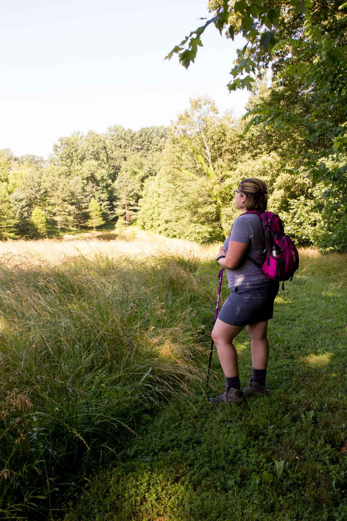 Brunette woman in hiking gear and a backpack, looking over a field.