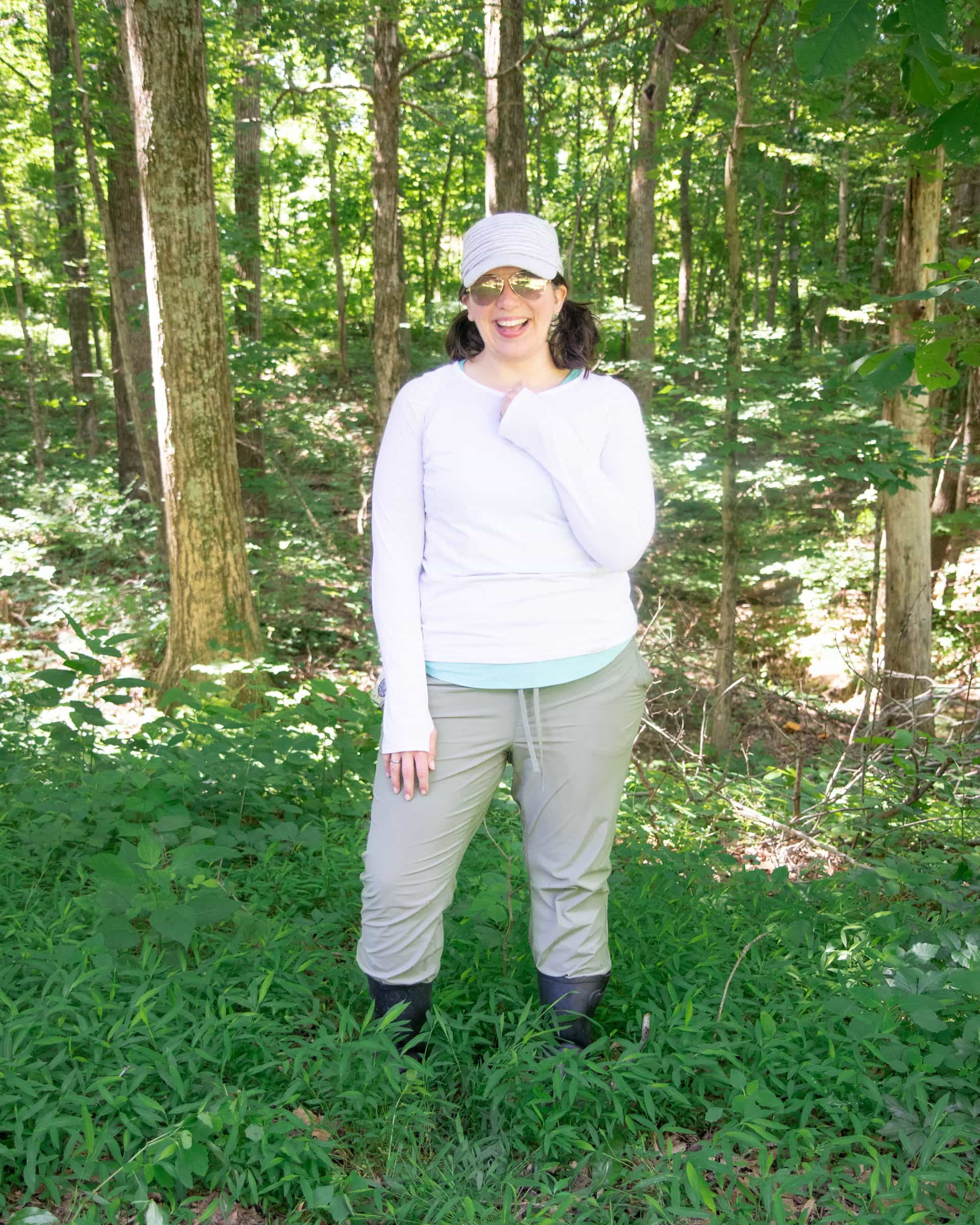Woman in long sleeve shirt, long pants, and a hat standing in the woods