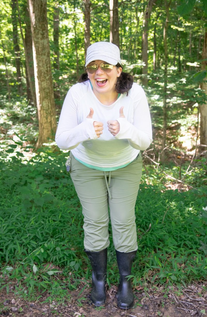 Woman in long sleeve shirt, long pants, and a hat standing in the woods and giving a thumbs up