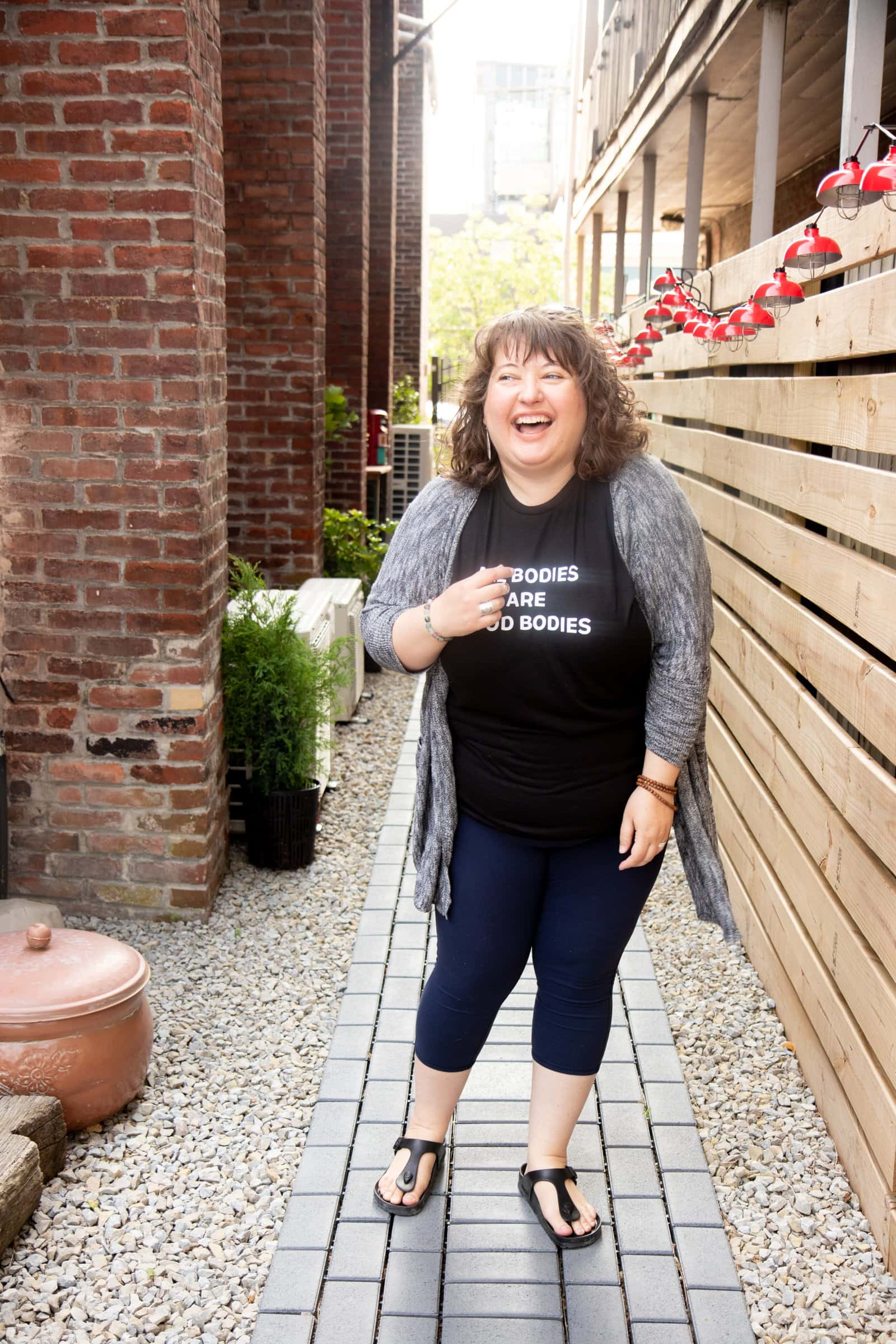 "Brunette curly-haired woman standing and laughing in a shirt that says ""All Bodies Are Good Bodies."""