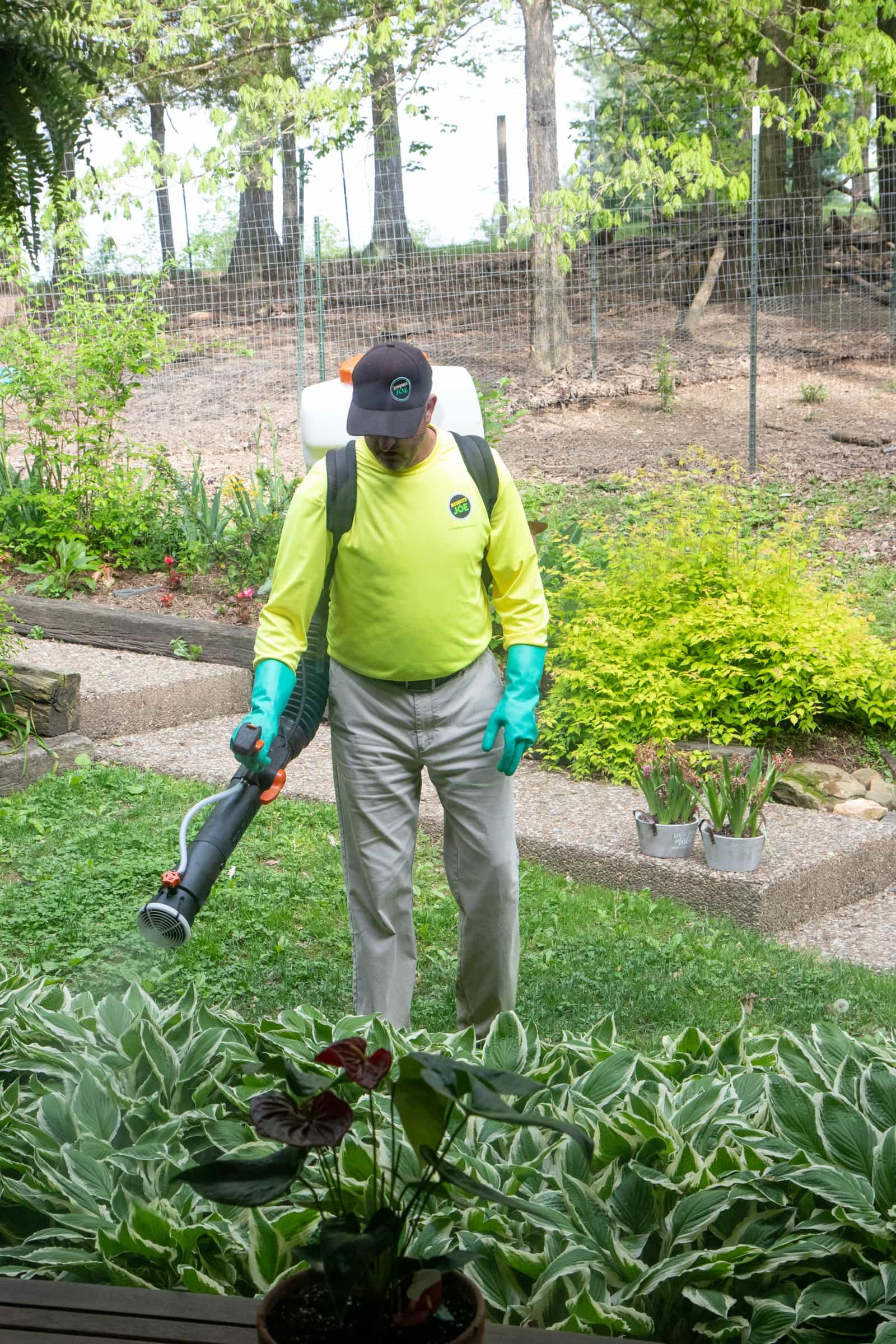 Man in protective gear providing a barrier spray to a yard to keep ticks away