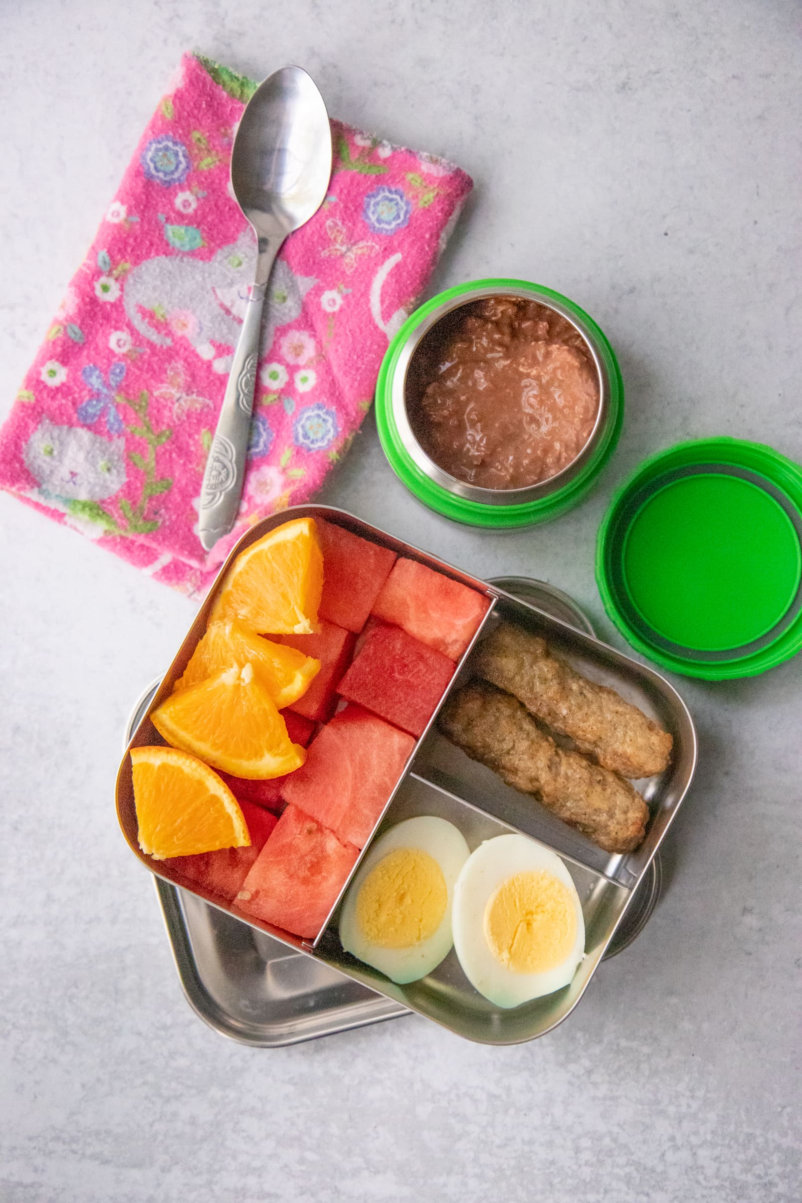 Waste-free packed lunch of sausage links, hard boiled egg, applesauce, and fruit.