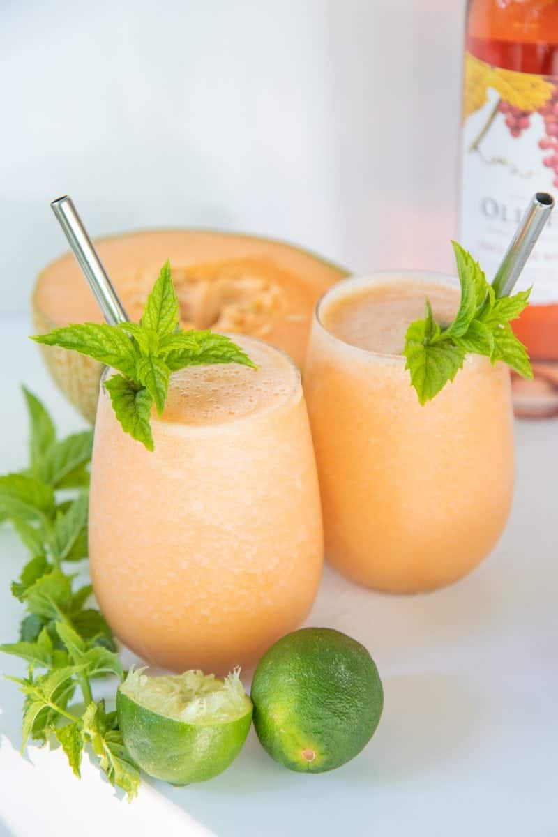 Two glasses filled with cantaloupe frosé, garnished with mint and straws. A halved cantaloupe and mint sprigs surround the glasses.