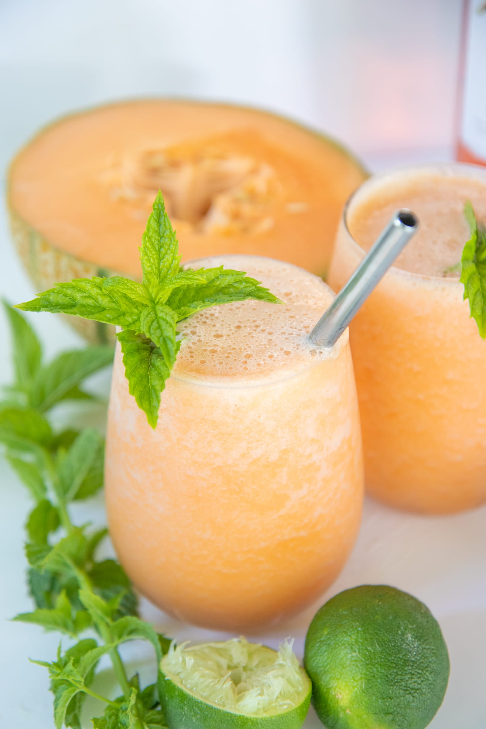 Two glasses with straws filled with cantaloupe frosé, garnished with mint. A halved cantaloupe and mint sprigs surround the glasses.
