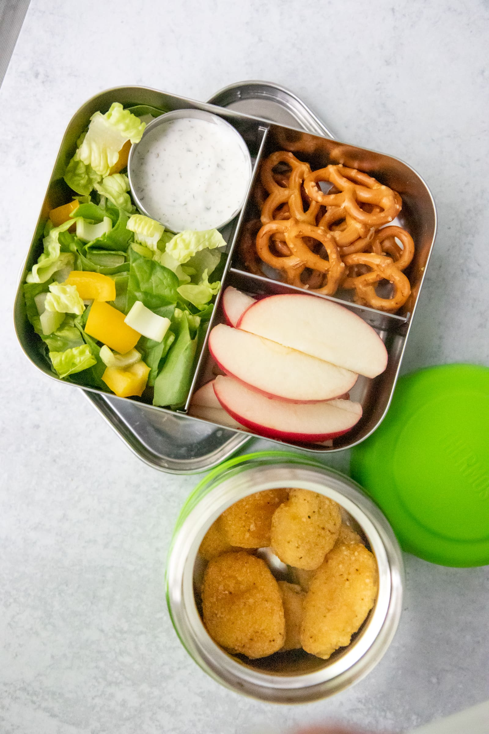 Chicken nuggets in a Thermos, next to a lunch box filled with salad, pretzels, and apple slices