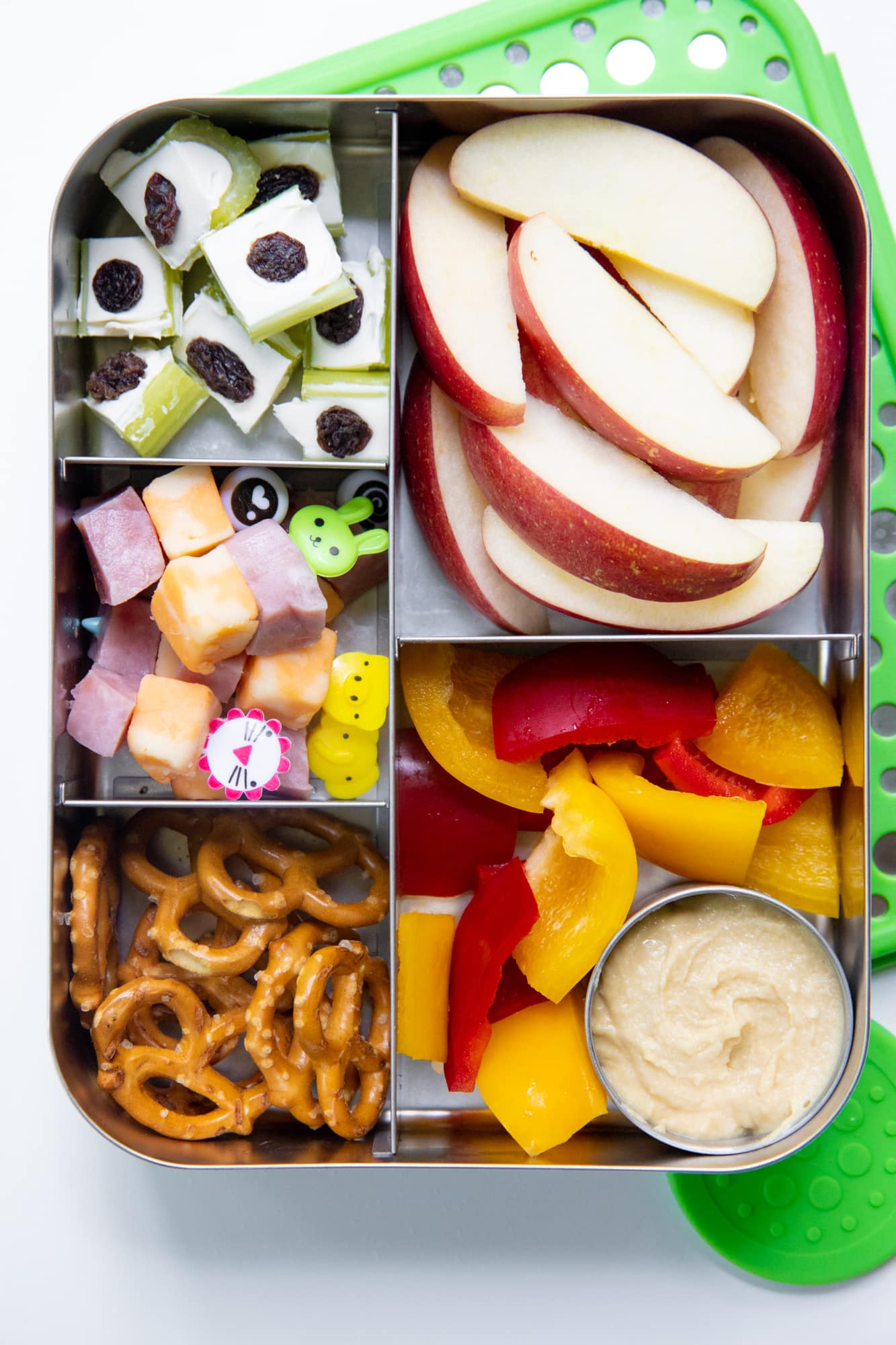Close-up of a bento-style stainless steel lunch box filled with apple slices, pretzels, ham and cheese on toothpicks, bell peppers and hummus, and stuffed celery, for a school lunch idea.