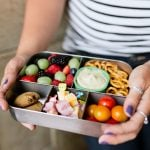 Hands holding a filled bento-style lunch box for a zero-waste lunch