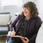 Brunette woman in a purple cardigan sitting on a white couch, laughing while she writes in a journal