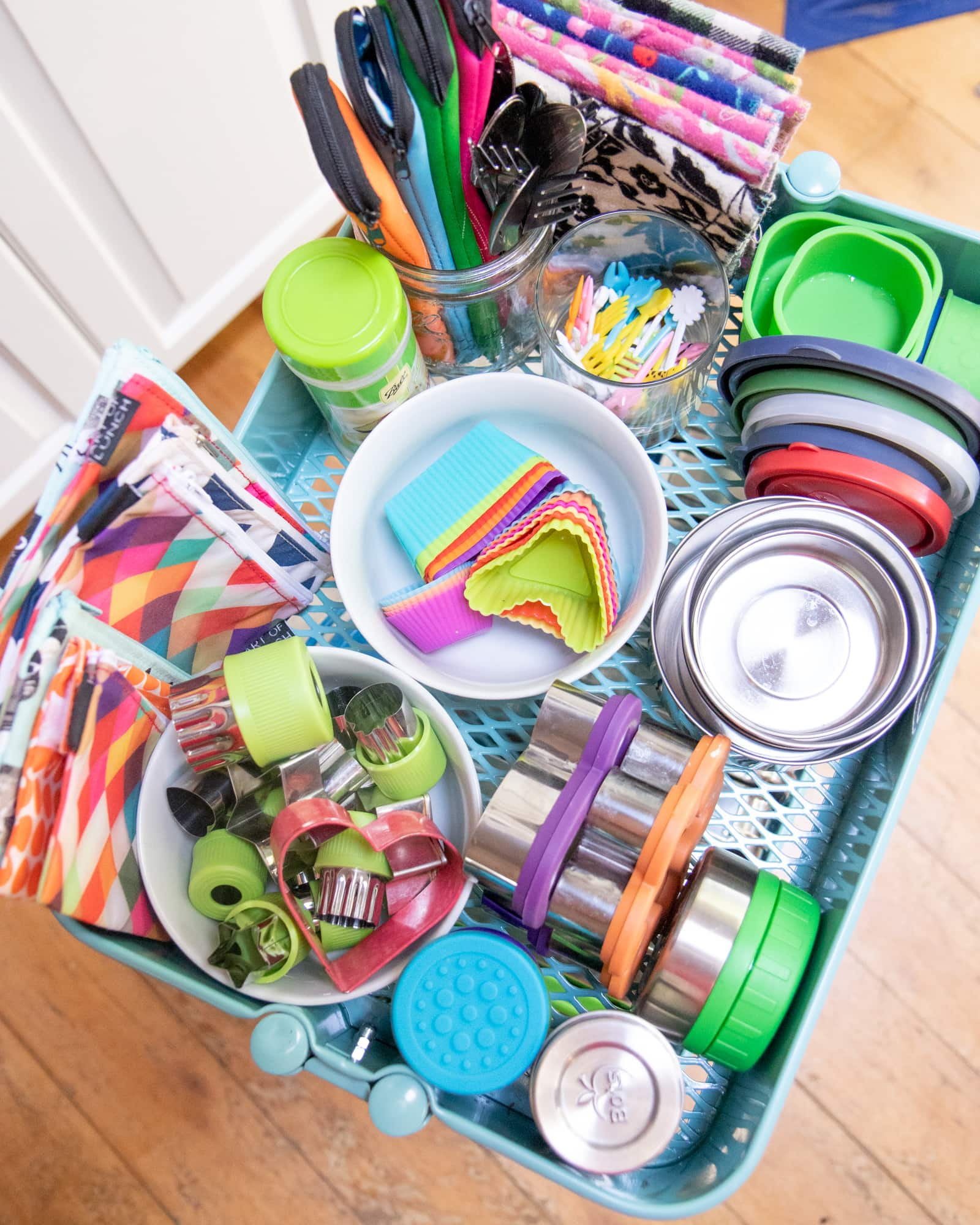 Shelf of a utility cart holding small containers and accessories for zero-waste lunch packing.