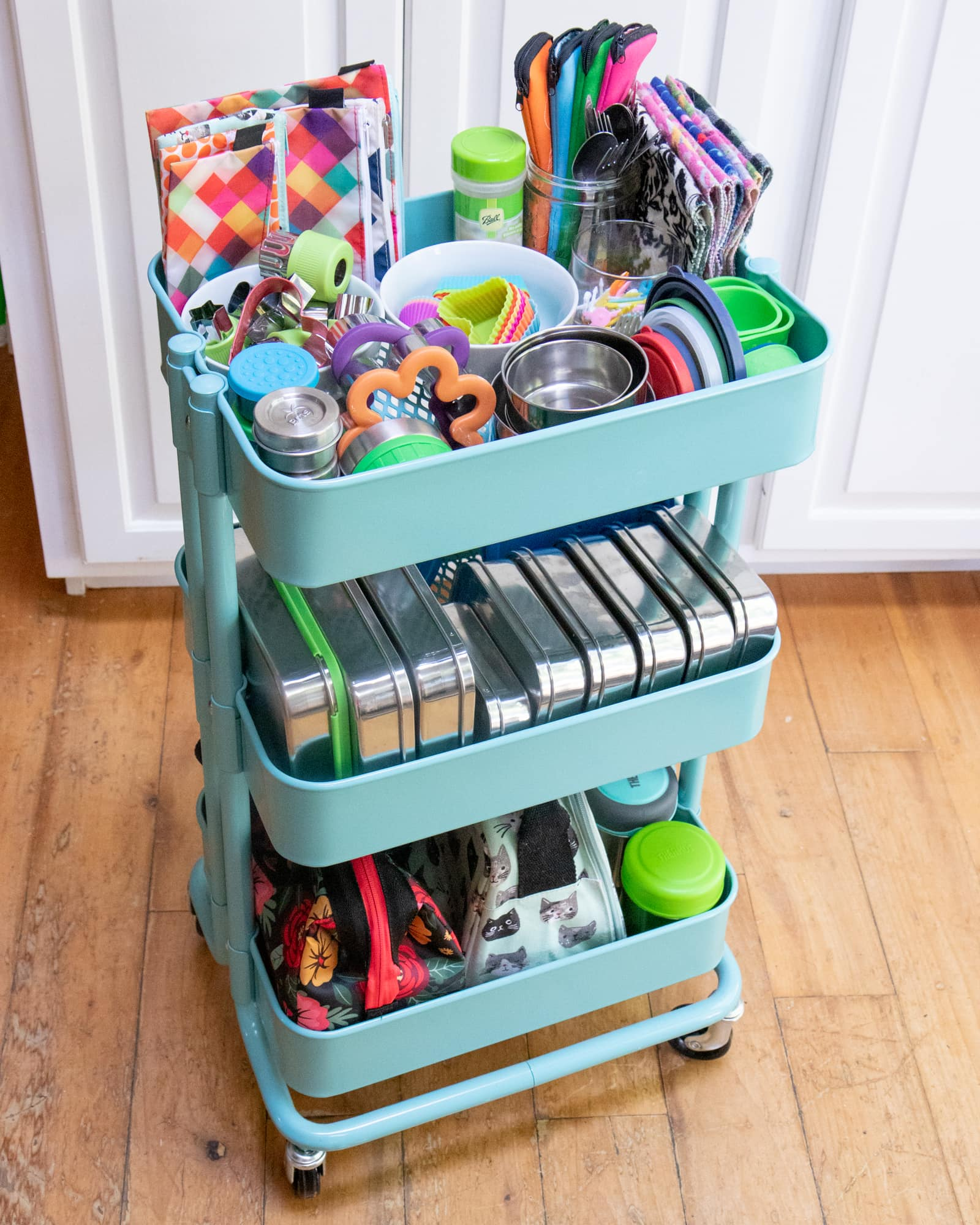 Rolling utility cart filled with tools and materials for packing zero-waste lunches.