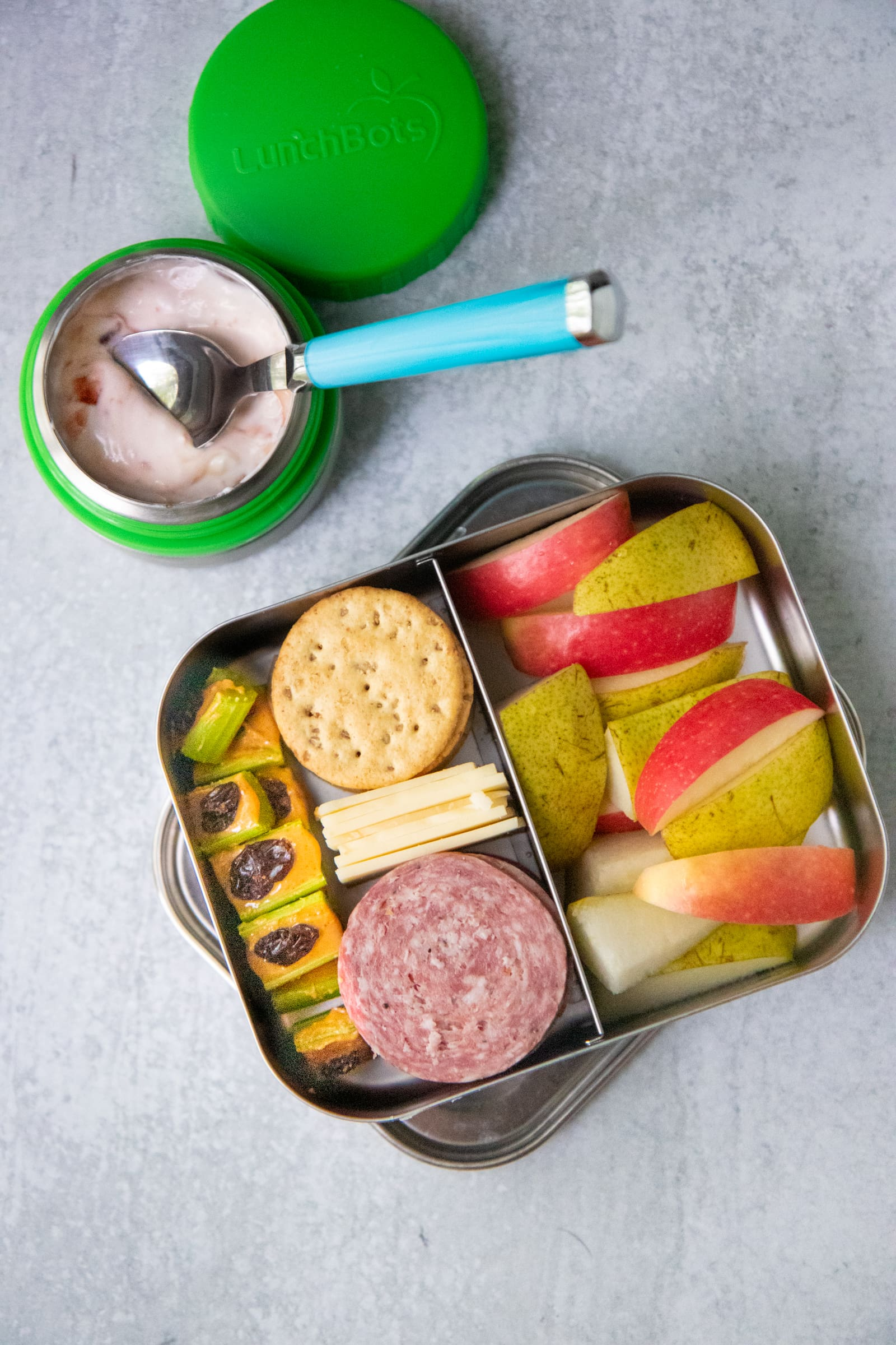 Divided lunch container filled with cheese, crackers, salami, fruit slices, and ants on a log. There is a container of yogurt next to it.