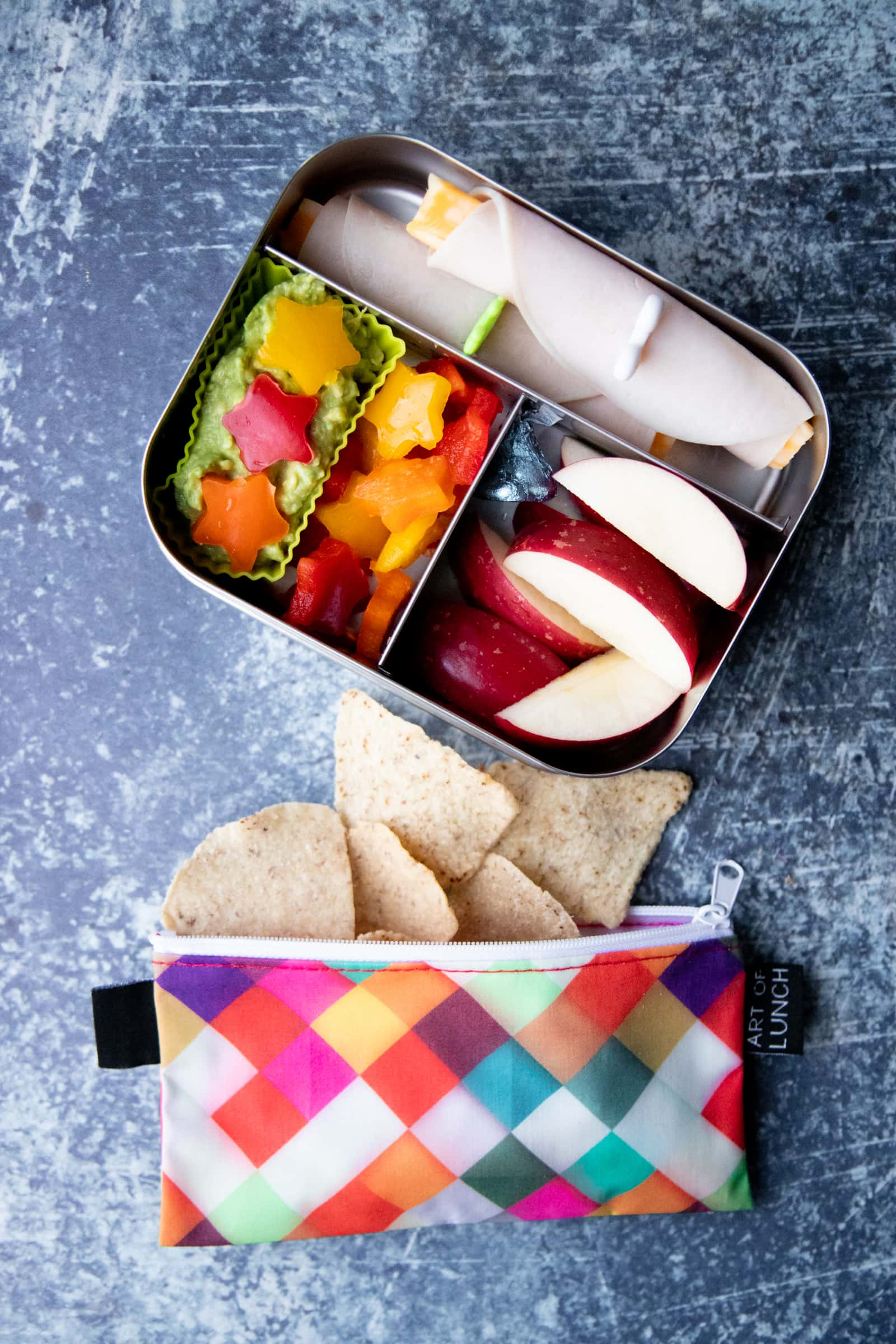 Packed school lunch of apple slices, bell pepper stars, guacamole, turkey and cheese roll-ups, and a bag of tortilla chips.