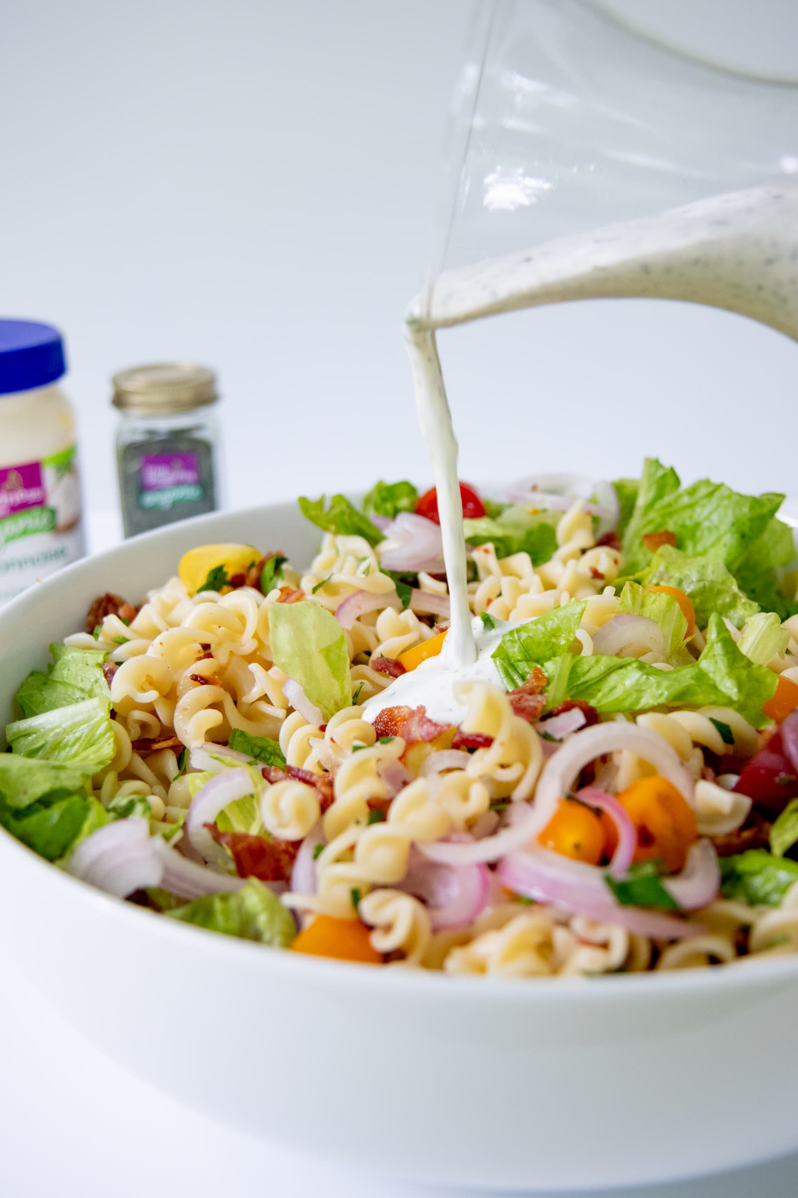 Homemade ranch dressing being poured over a pasta salad