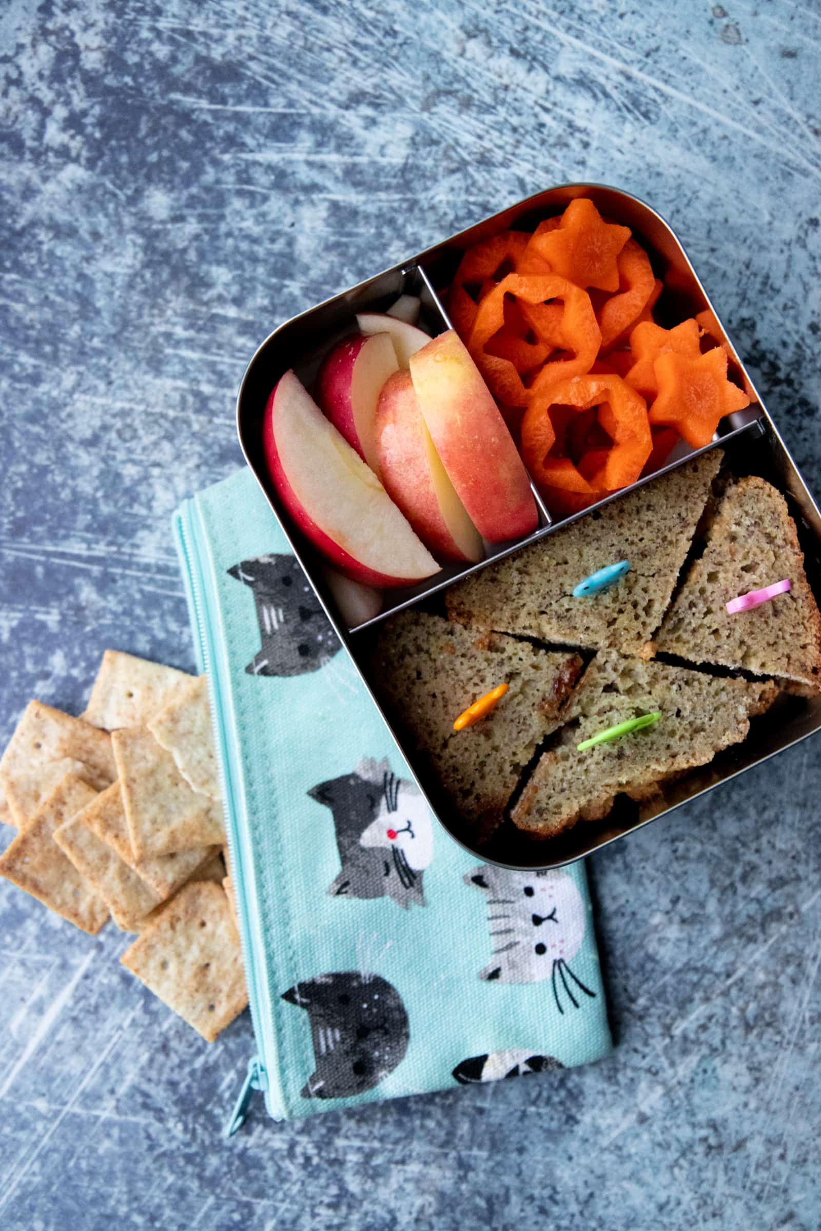 Steel lunchbox on top of a bag of crackers. The lunch box holds a sandwich, apple slices, and carrots cut into stars.