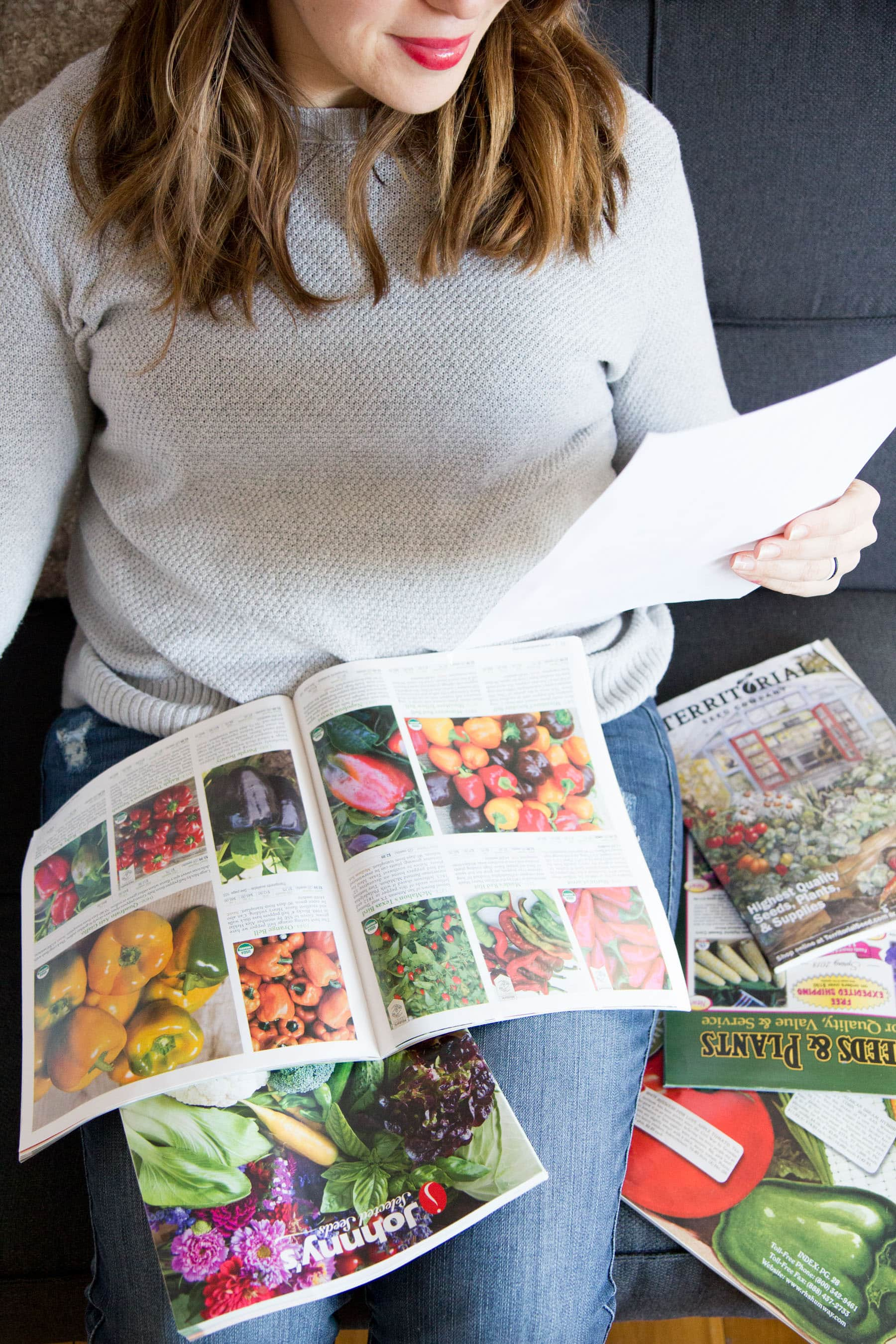 Torso of a woman looking through seed catalogs