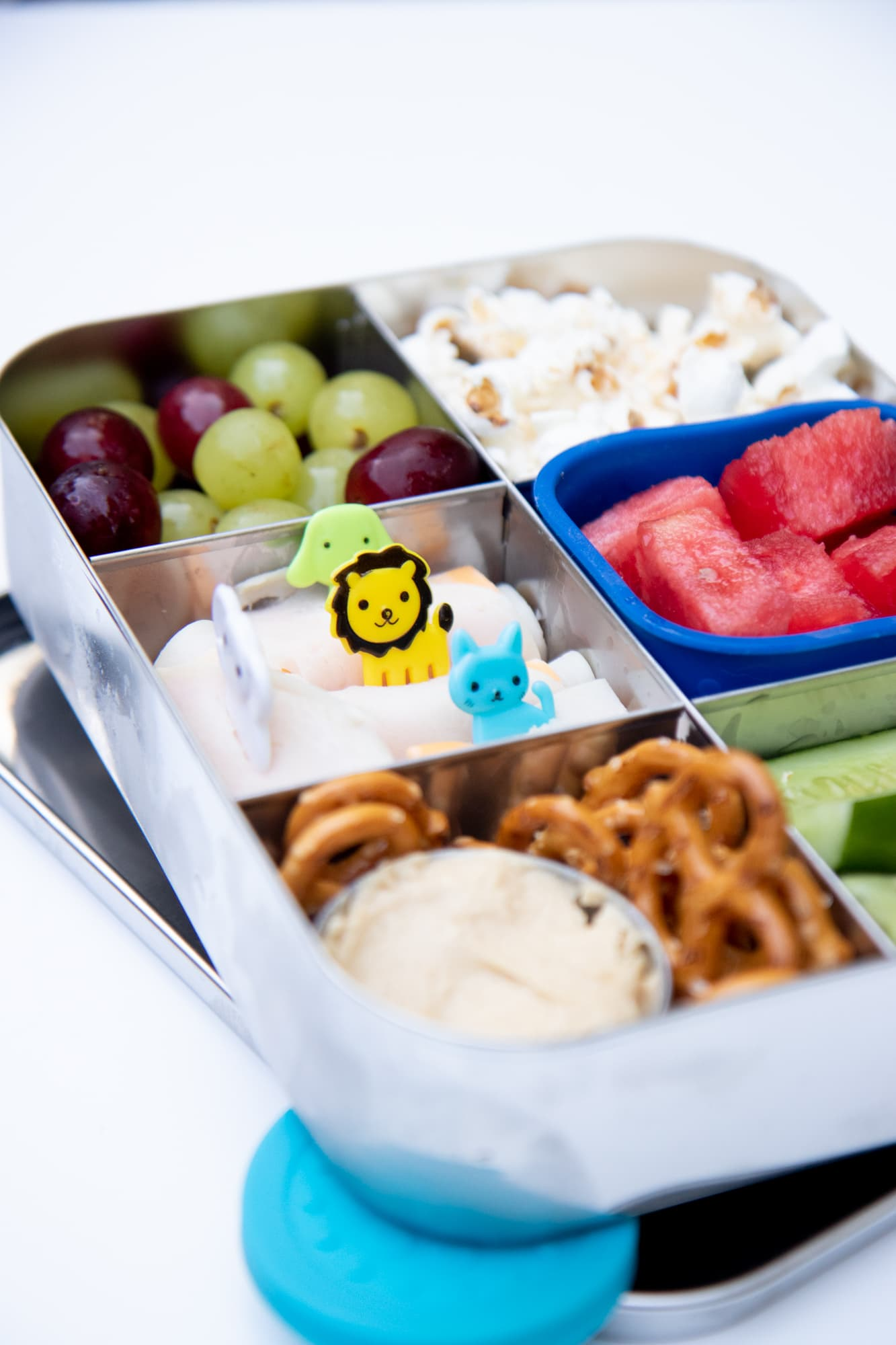Stainless steel bento-style lunchbox filled with a snack lunch: pretzels and dip, grapes, watermelon, popcorn, cucumber spears, and deli meat roll-ups