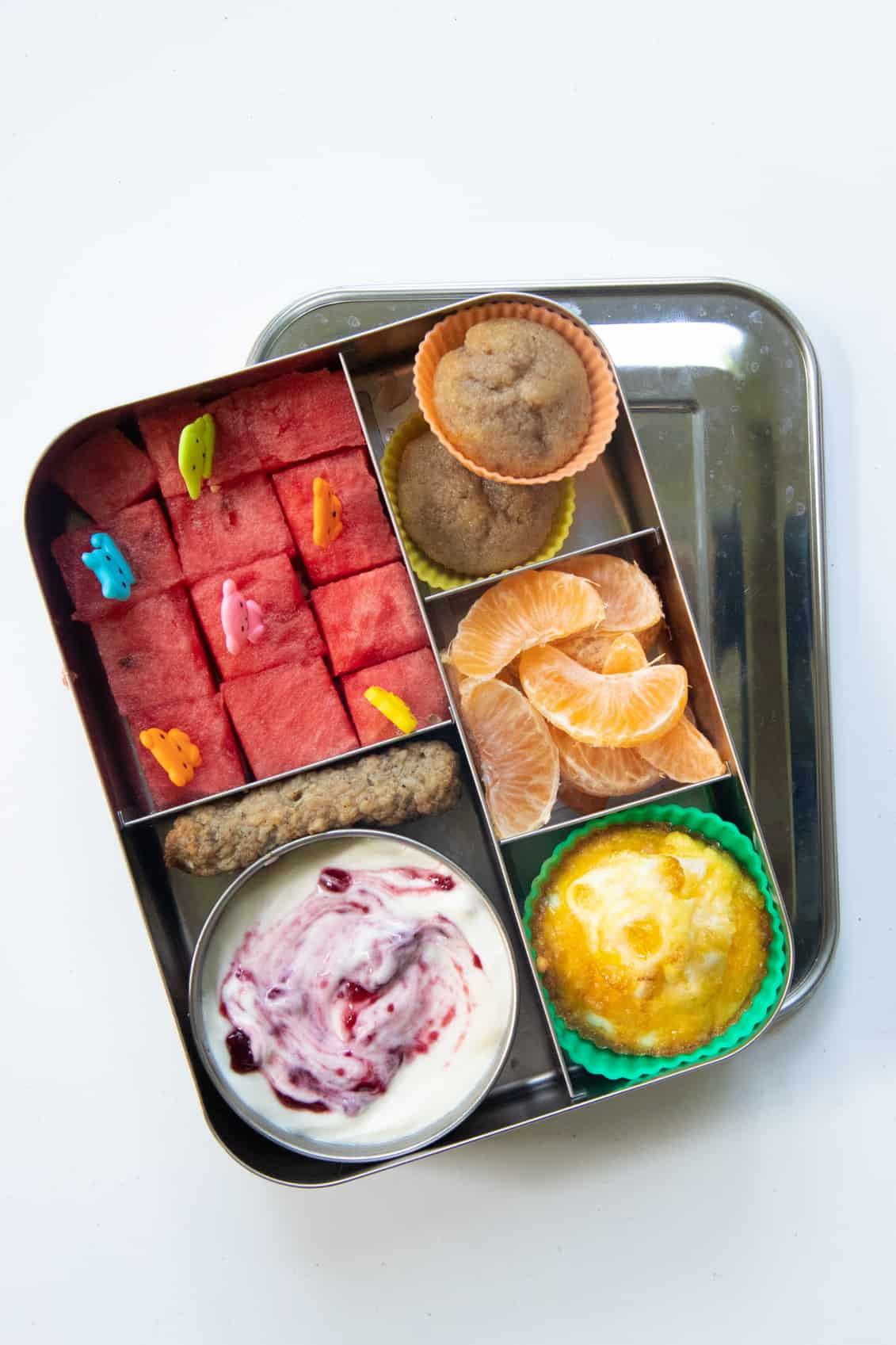 Stainless steel lunchbox packed with brunch foods: watermelon cubes, muffins, egg cup, clementine, yogurt.