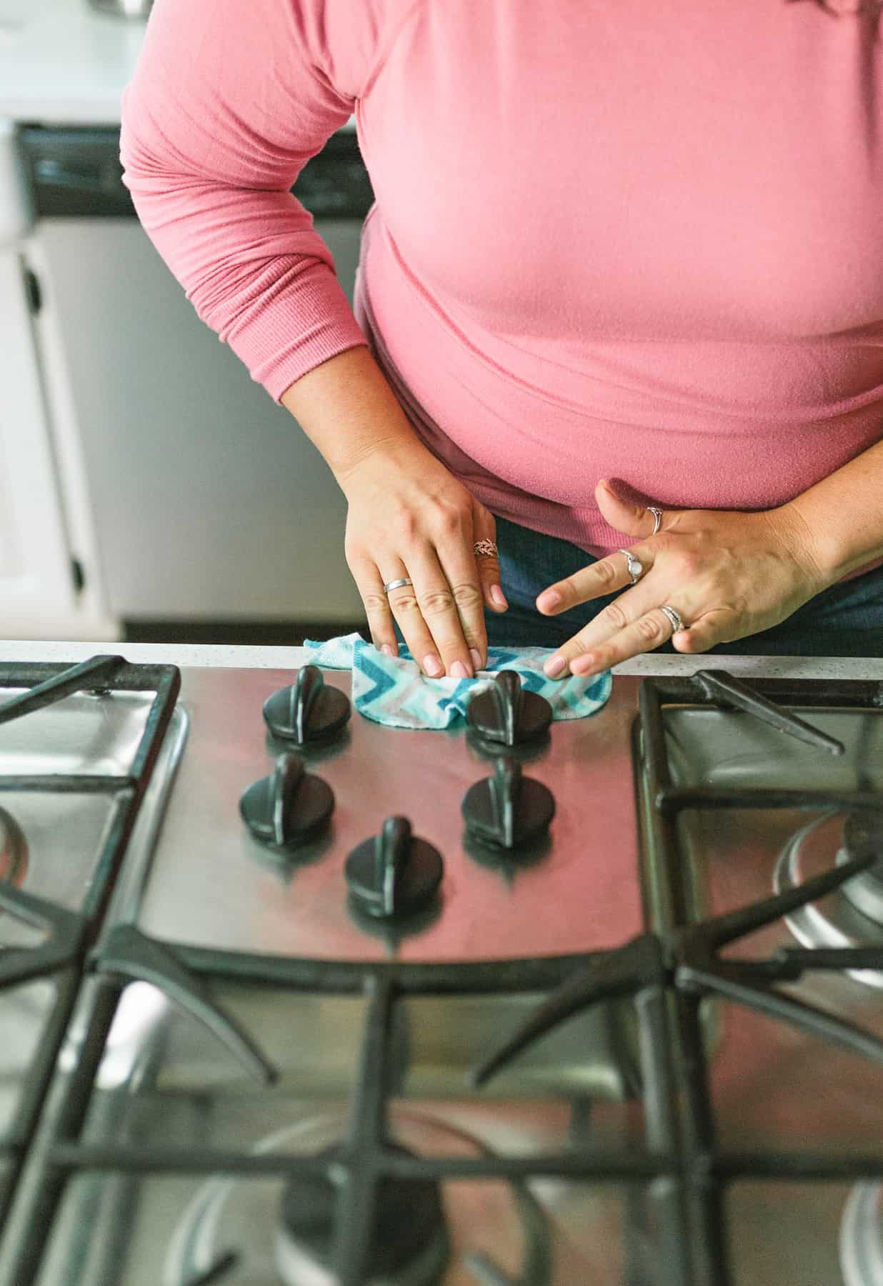 Woman using a reusable cleaning wipe to clean a stovetop.