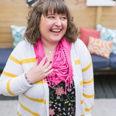 Brunette woman in a pink scarf and striped cardigan laughing and looking off to the side.
