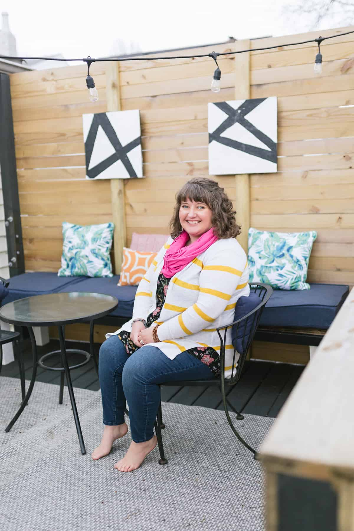 Brunette woman in a pink scarf and striped cardigan, sitting on a patio and smiling.