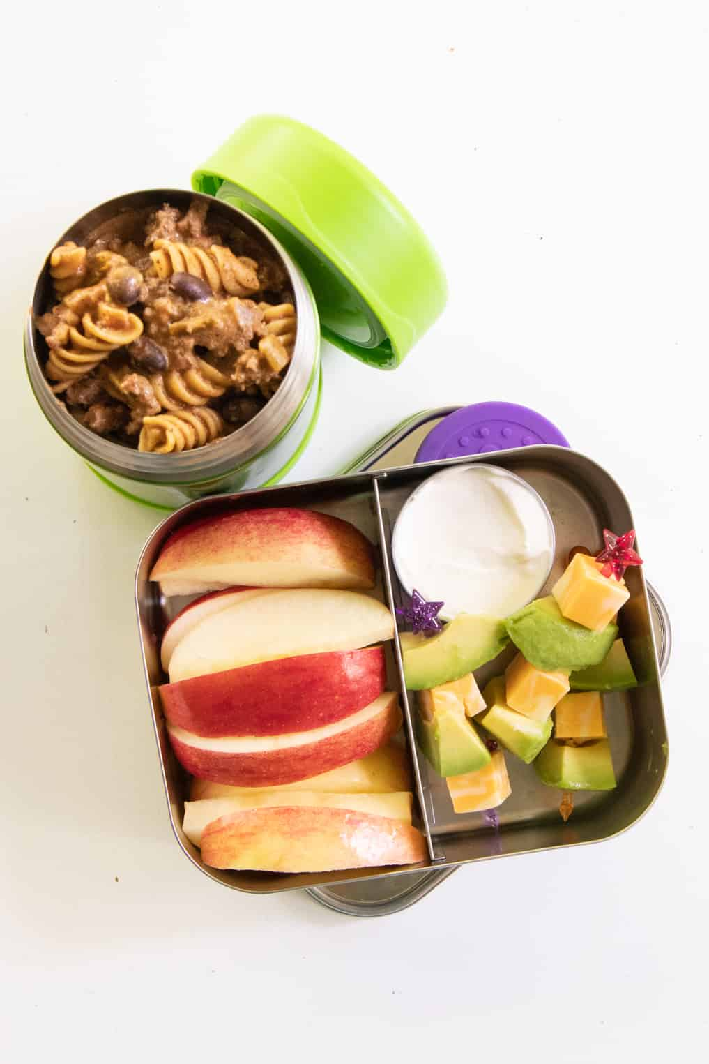 Stainless steel lunchbox with fruit and cheese and avocado skewers, next to a Thermos of taco macaroni skillet.