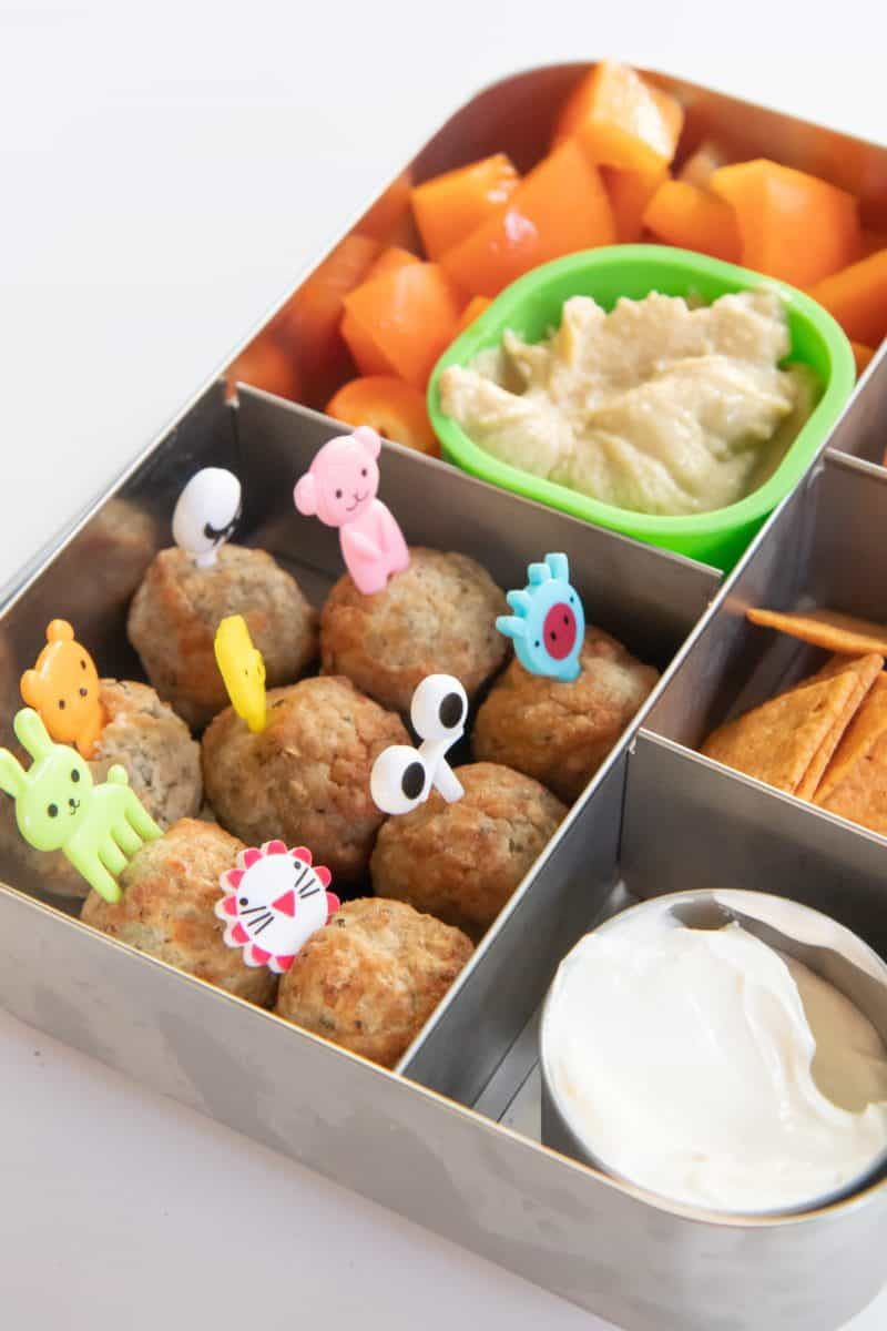 Bento-style lunchbox filled with meatballs, cantaloupe, crackers, and hummus