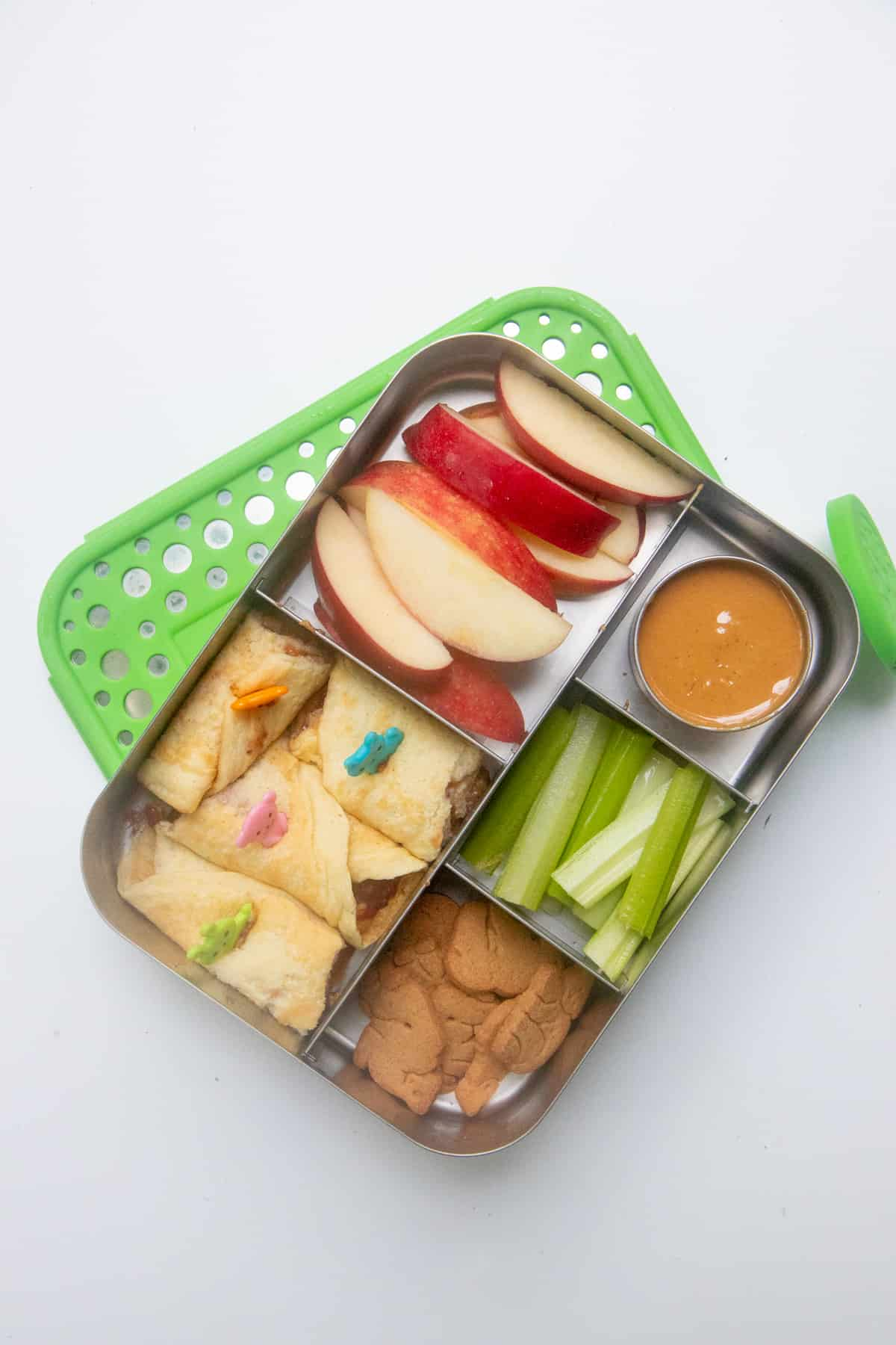 Stainless steel lunch box with pancake roll-ups, apple slices, celery, and animal crackers.