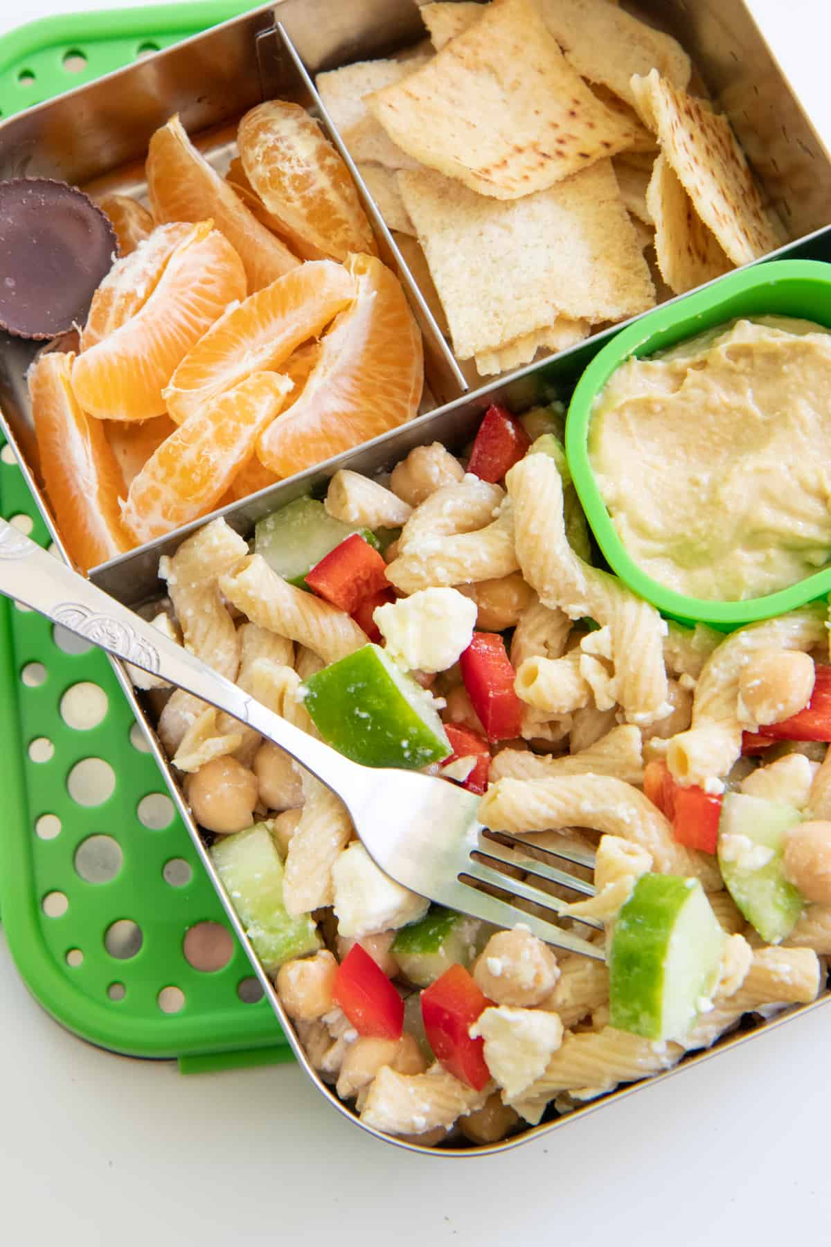 Stainless steel lunchbox with pasta salad, orange slices, and pita chips for a school lunch.