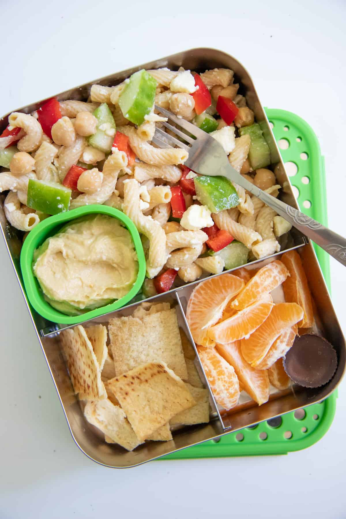 School Lunch Ideas: Stainless steel lunch box with Greek pasta salad, pita chips and hummus, and clementine slices.