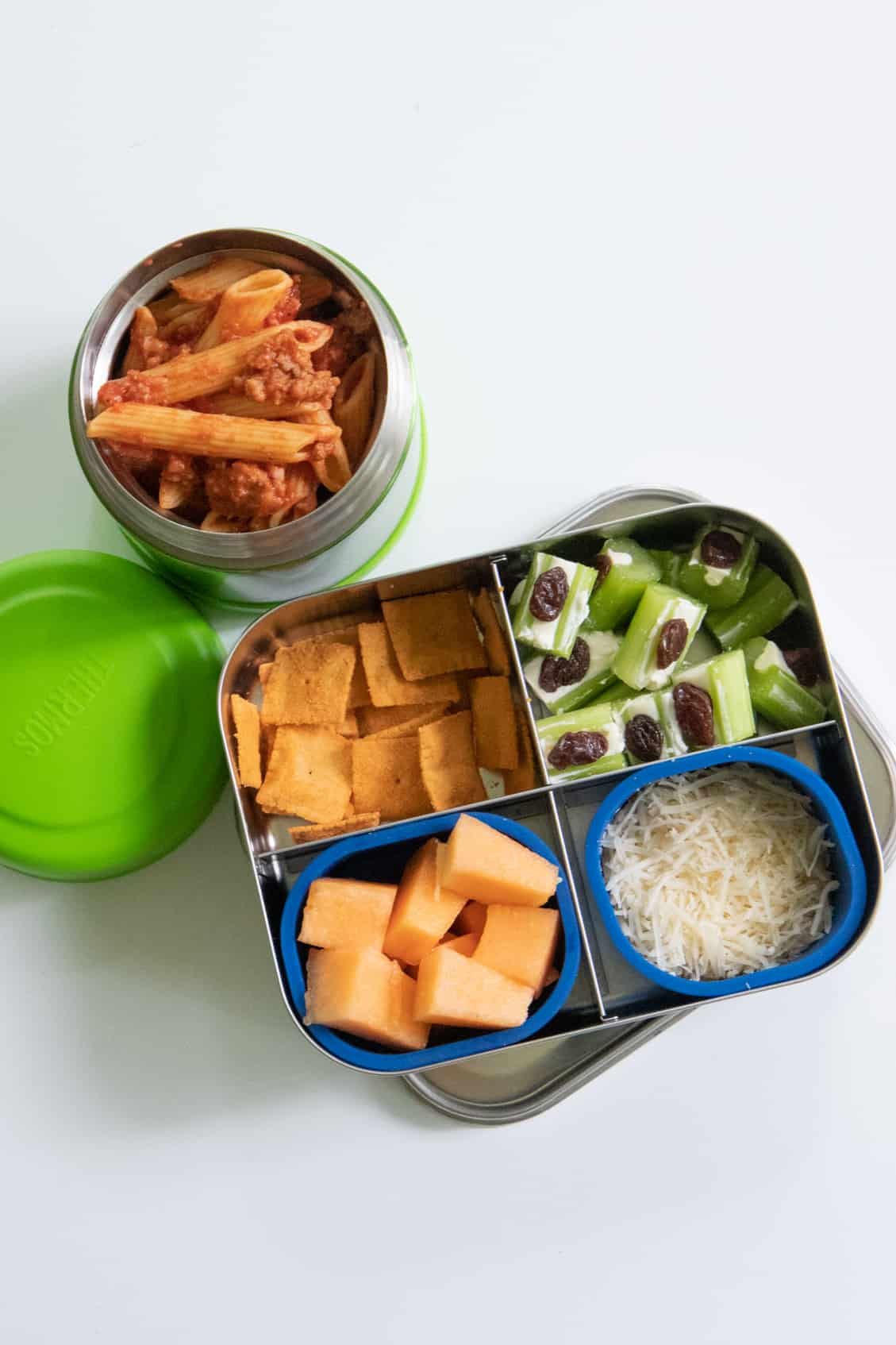 Stainless steel lunch box with cantaloupe, ants on a log, and crackers next to a Thermos of penne in meat sauce.