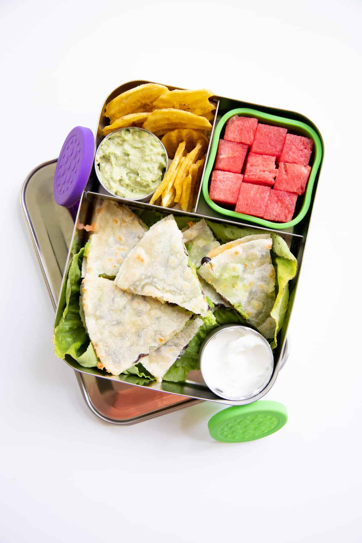 Stainless steel divided lunchbox with quesadilla, watermelon, plantain chips, and guacamole
